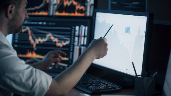 Analyzing data. Close-up of young businessman pointing on the data presented in the chart with pen